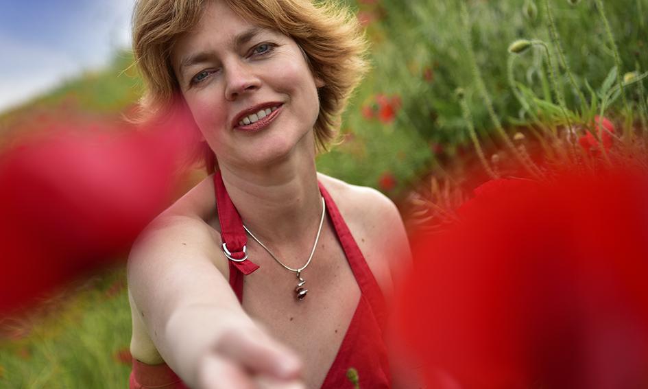 Mooie vrouw met rode jurk in veld klaprozen 4