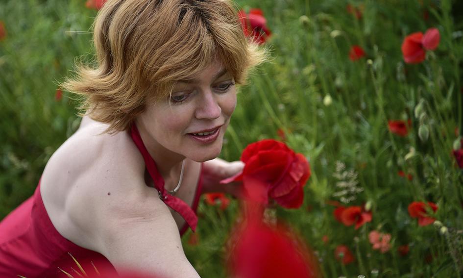 Mooie vrouw met rode jurk in veld klaprozen 2