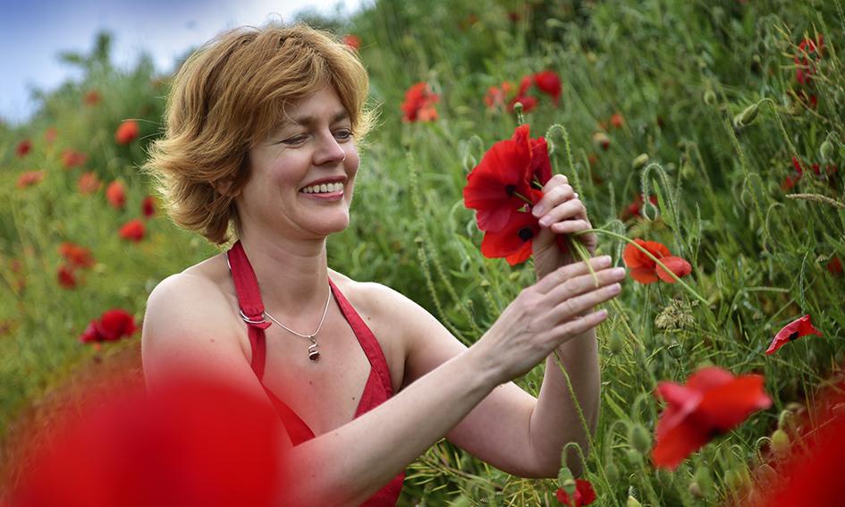 Mooie vrouw met rode jurk in veld klaprozen 3