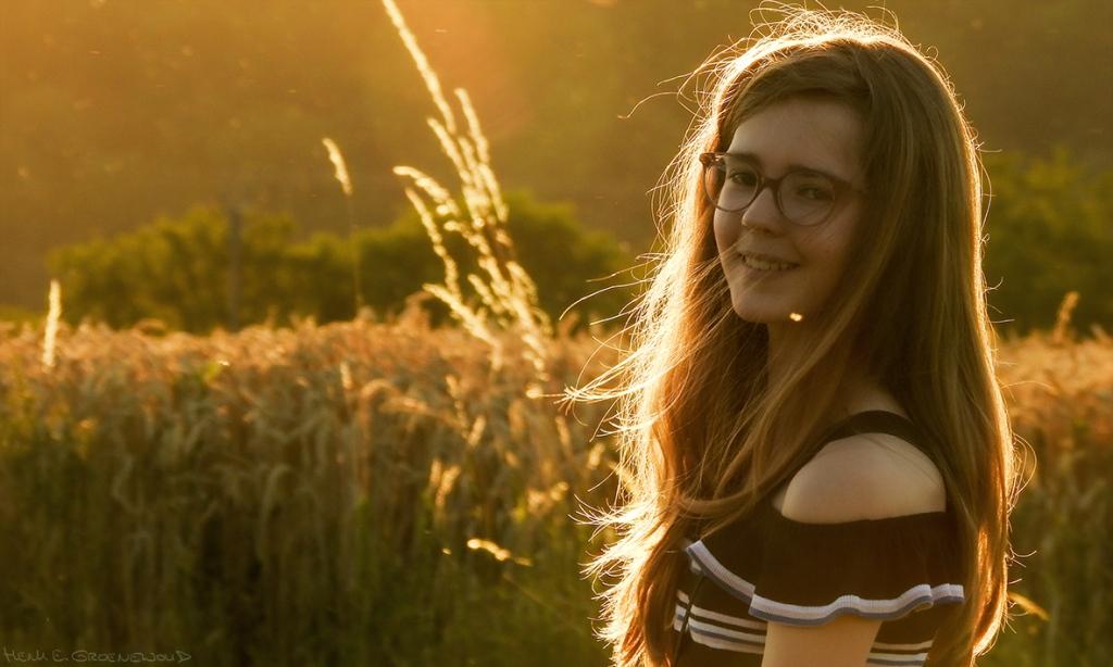 Portret van meisje in gouden zonlicht met stralenkrans door de zonsondergang